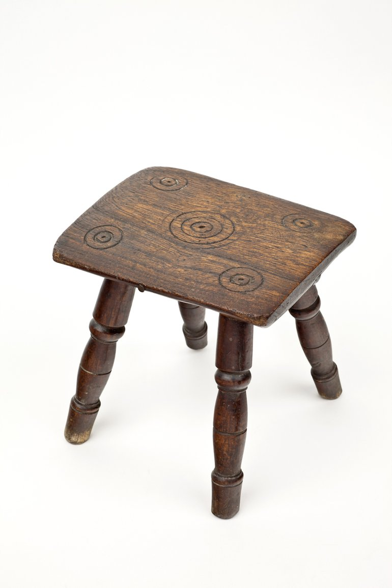 Witches Stool from Anne Hathaway's Cottage, C16th. Small wooden foot stool carved with five sets of rings known as 'Witches Marks'.