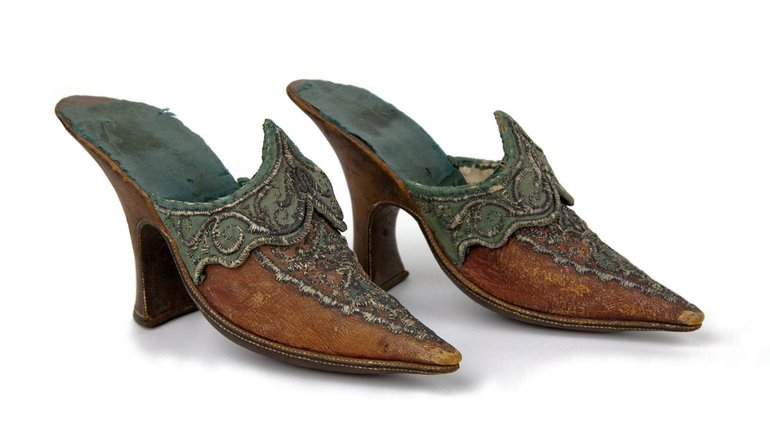 Shoes, c. 1760-1770. A pair of women's shoes, said to have been worn by Mrs Garrick at the Garrick Jubilee of 1769. They are made from red leather and trimmed and partly lined with blue/green silk, and decorated with metal thread. Shoes are backless, with